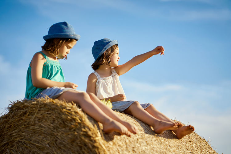 Low angle view of friends wearing hats sitting on hay bale against sky
