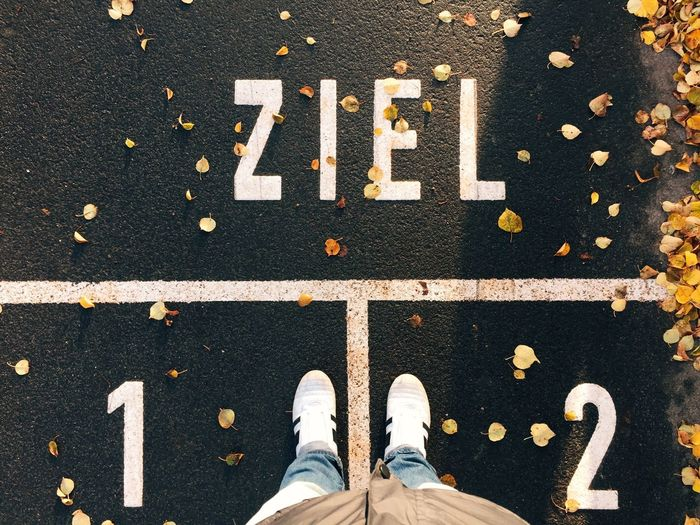 Goal line in German Ziel Goal Target LINE Sport Track Person Personal Perspective Feet Shoes Looking Down Bottom German Germany Berlin Word Text Street Marking Road Marking