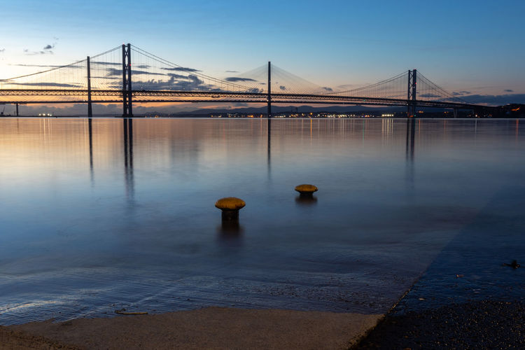 Forth Road Bridges, Sunset Sky Water Bridge Bridge - Man Made Structure Transportation Connection Nature Built Structure Architecture No People Reflection Suspension Bridge Travel Destinations River Tranquil Scene Blue Sunset Outdoors Bay Wooden Post Scotland