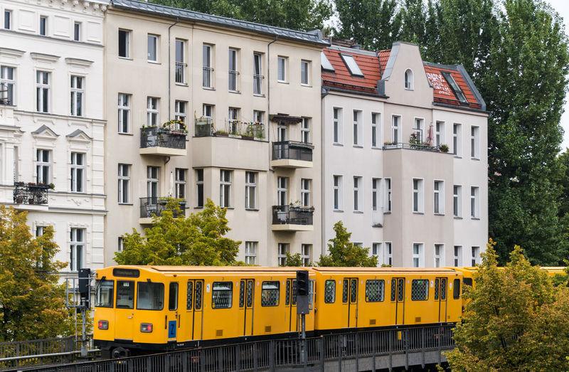 Yellow metro train against building
