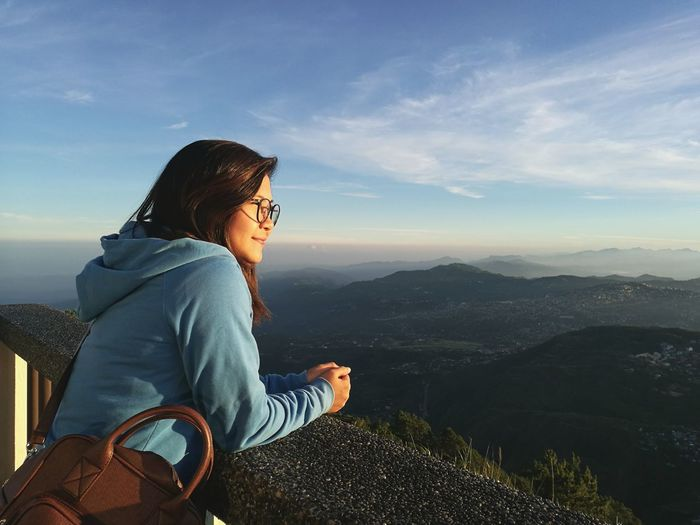 Side view of woman looking at landscape on mountain against sky during sunset