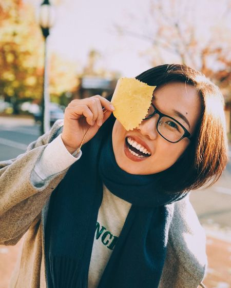Portrait of smiling young woman holding leaf