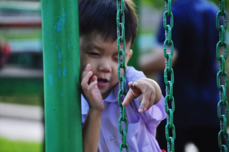 Cute boy winking while gesturing amidst outdoor play equipment at playground