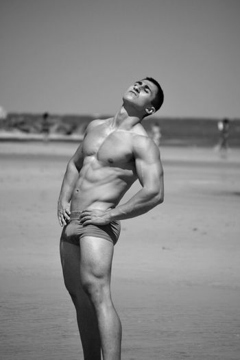 Shirtless Muscular Man Standing At Beach Against Clear Sky