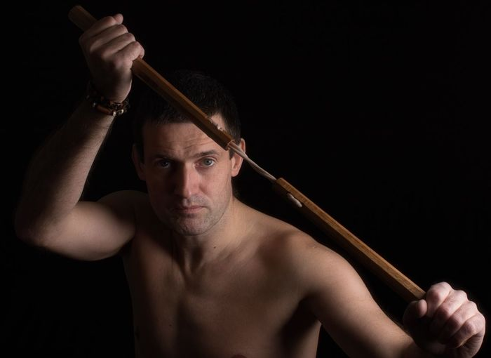 Portrait of shirtless man with knife against black background