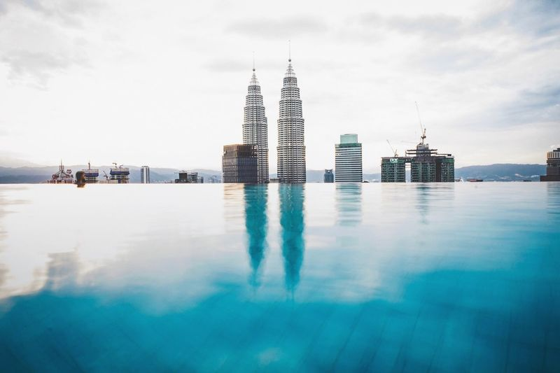 Reflection Of Buildings In Infinity Pool Against Sky