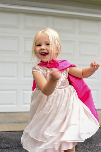 Cute little blonde girl playing dress up - superhero princess in the driveway Beautiful Children Dress Kids Light Princess Beauty Blond Hair Cape  Child Childhood Dress Up Dressing Up Expression Face Innocence Kid Light And Bright Looking At Camera Models On Monochrome Play Playing Portrait Preschooler Smiling White Background