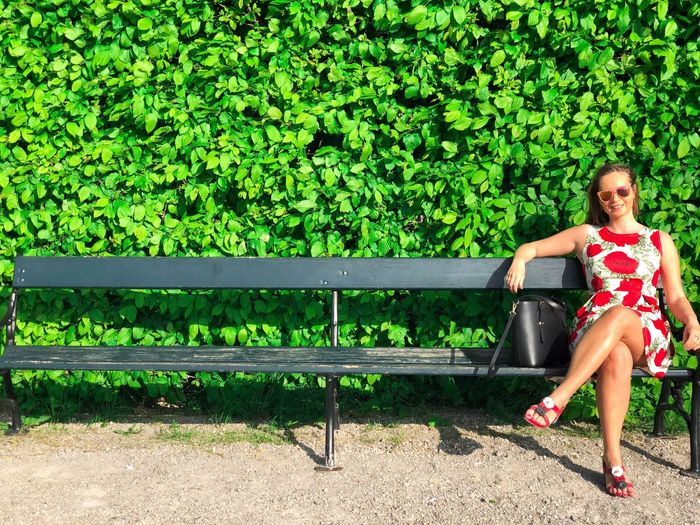 Portrait of woman sitting on bench against plants