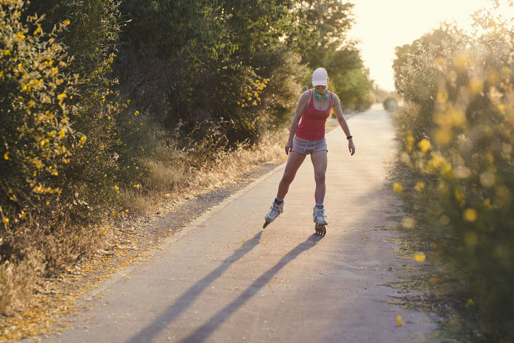 Young woman having fun while roller skating outdoors during female wearing a pale pink cap, headphones and sports clothes doing exercise. Casual Clothing Day Full Length Leisure Activity Lifestyles Motion Nature One Person Outdoors Plant Real People Rear View Road Running Shadow Shorts Sport Sunlight Transportation Tree Women