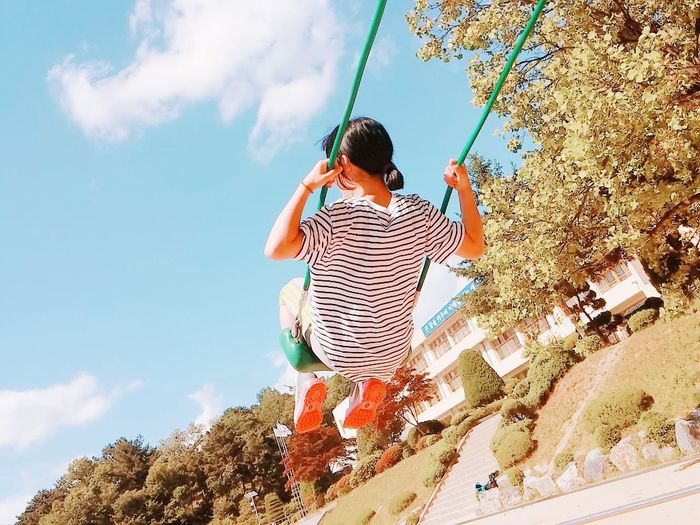 Low angle view of young woman swinging against sky
