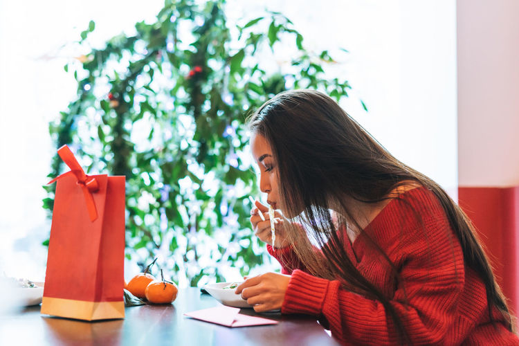 Beautiful smiling young asian woman in red clothes eating asian food in chinese  restaurant