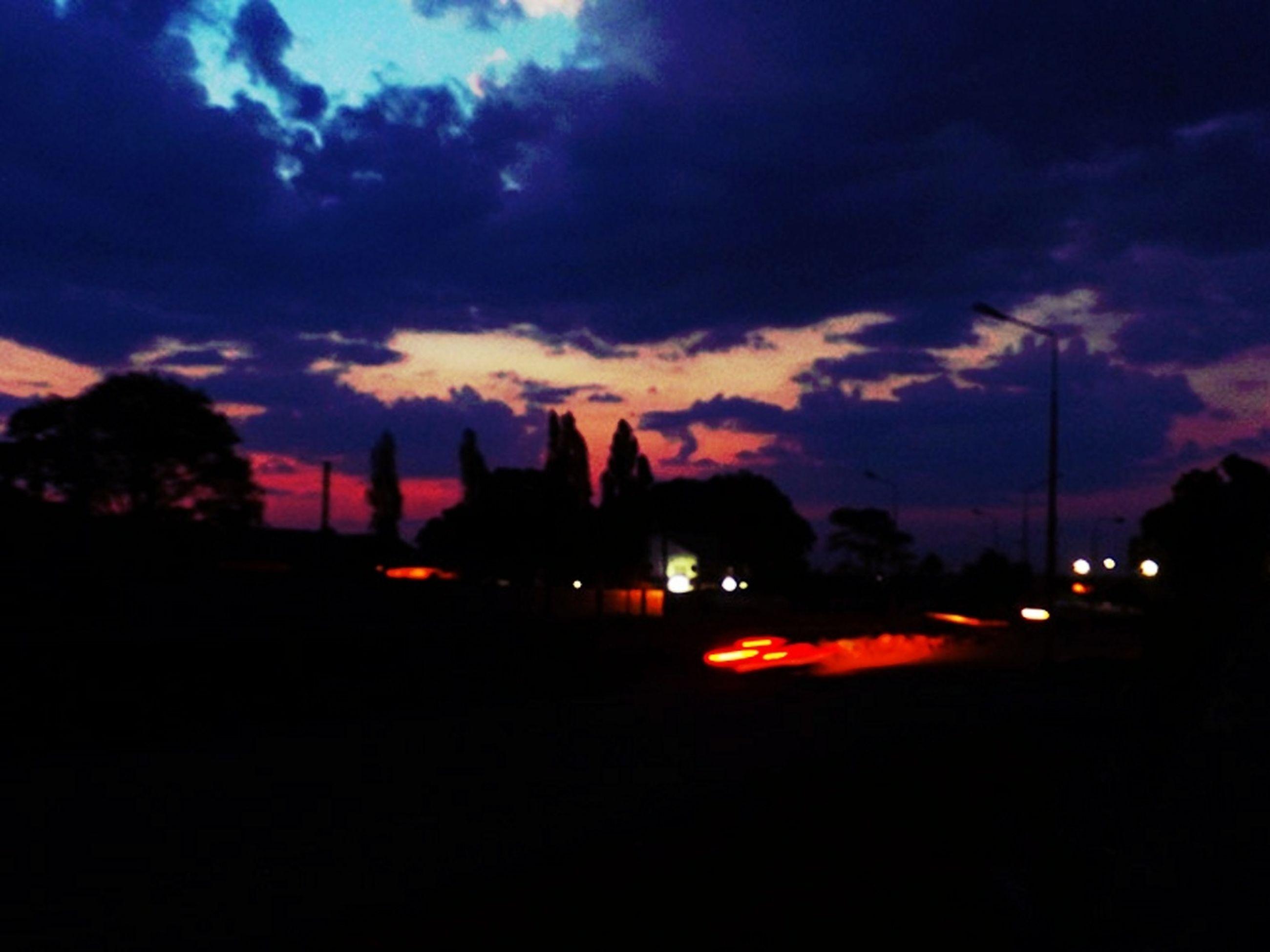 illuminated, sky, sunset, silhouette, building exterior, cloud - sky, city, street light, night, dusk, built structure, architecture, dark, tree, car, street, dramatic sky, cloud, transportation, road