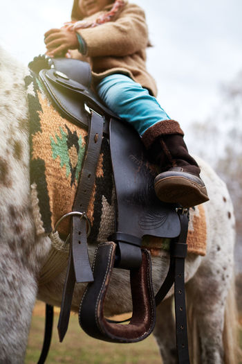 Close-up of man holding camera hanging outdoors