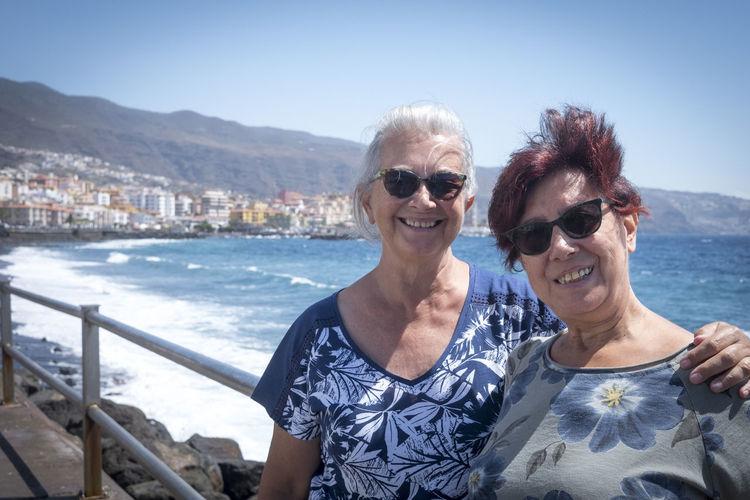 Portrait of smiling senior friends standing against sea