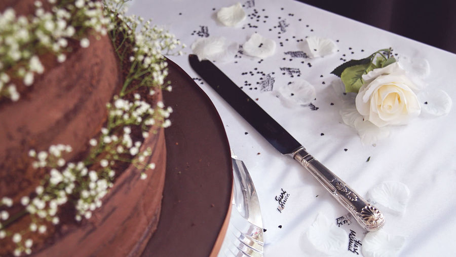 Flower-lined chocolate wedding cake Cake Cakes Chocolate Chocolate Cake Dessert Flower Flowers Food And Drink High Angle View Knife Marriage  Married Petals Plate Roses Rose🌹 Table Wedding Wedding Cake Wedding Photography