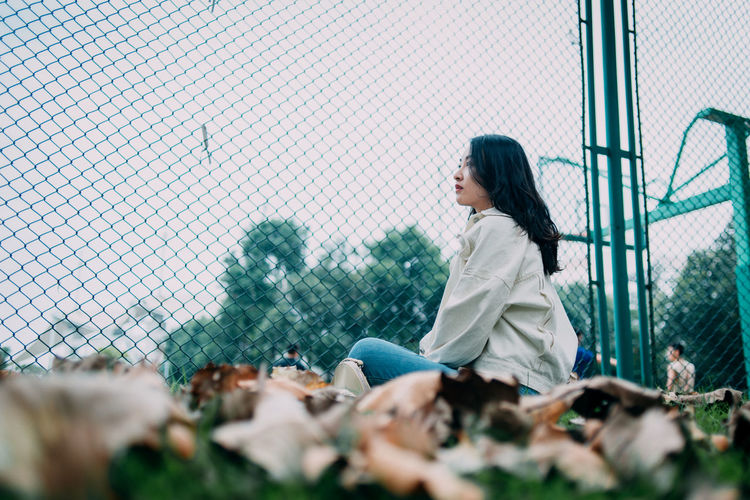 Surface level view of young woman sitting against chainlink fence