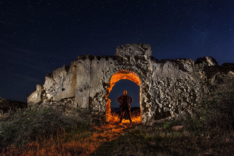 Full length of man standing by old ruins against sky at night