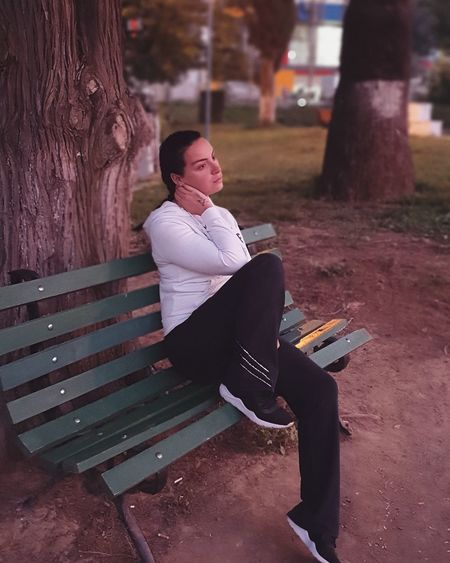 Young woman sitting on bench at park