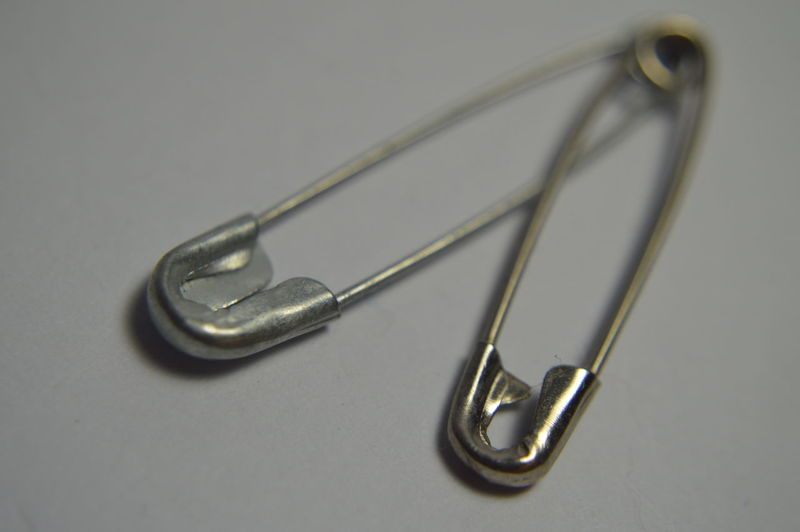 Close-up of safety pin on gray background