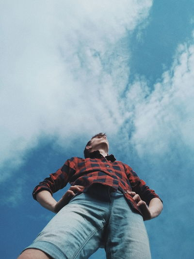 Low angle view of teenage boy standing against blue sky