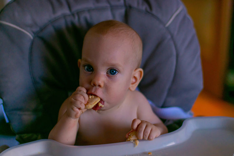 Close-up portrait of baby boy eating food on high chair
