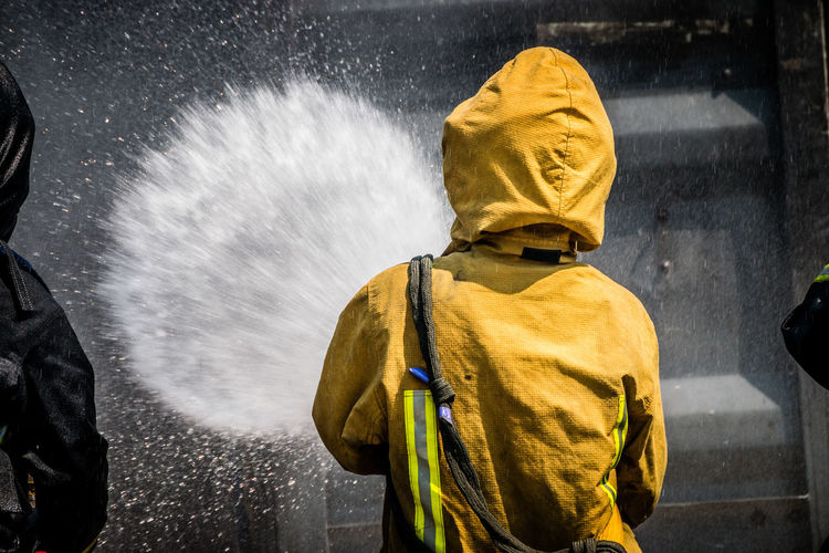 Rear view of person spraying water on wall