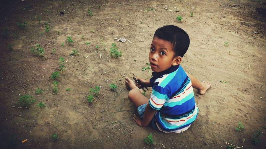 High Angle View Of Boy Looking Up While Playing In Dirt On Land