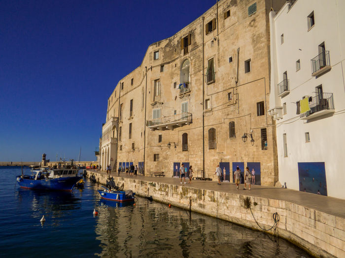 Boats moored in canal by buildings against clear sky