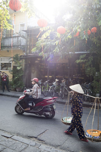 People riding motor scooter on street in city