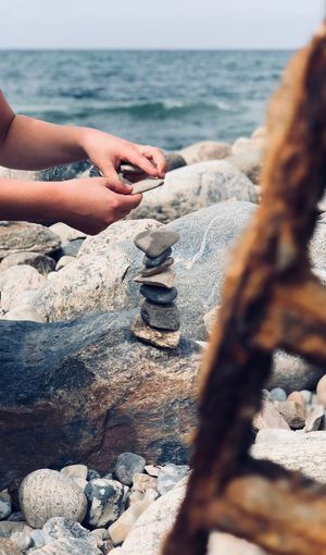 Cropped hands of woman stacking rocks at beach