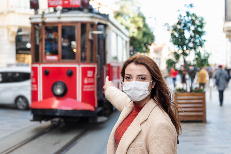 Portrait of woman wearing mask pointing at cable car street in city