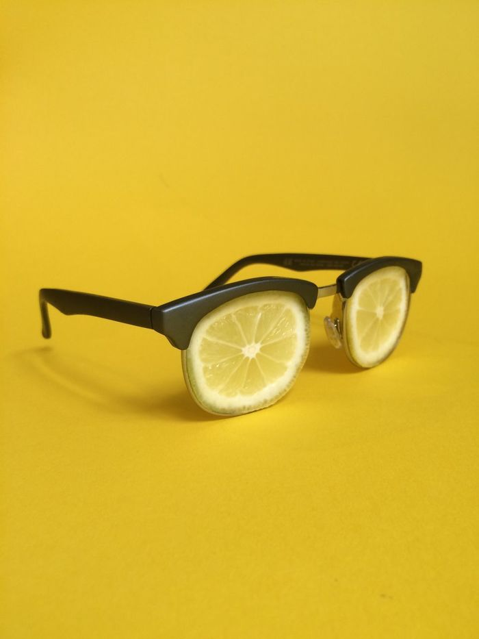 Eyeglasses made by lemon slices against yellow background