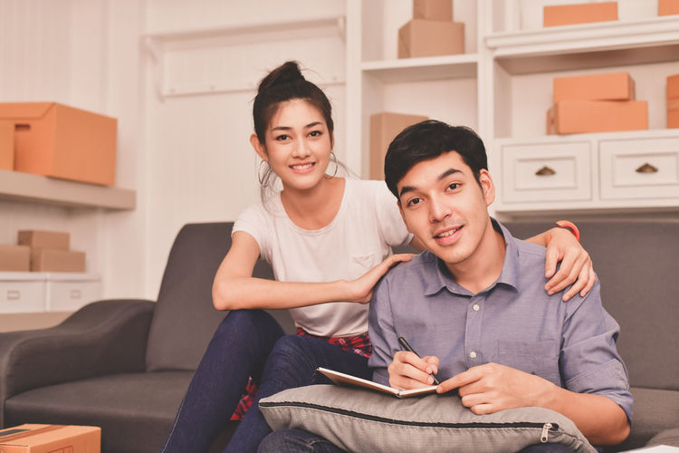 Casual Clothing Couple - Relationship Domestic Life Emotion Front View Furniture Happiness Holding Indoors  Lifestyles Looking At Camera Portrait Sitting Smiling Sofa Three Quarter Length Togetherness Two People Young Adult Young Men Young Women