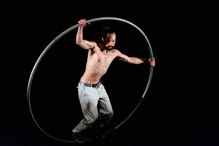Circus Arms Raised Balance Black Background Circle Front View Full Length Geometric Shape Holding Human Arm Indoors  Lifestyles Men Motion One Person Plastic Hoop Shirtless Skill  Sport Standing Strength Studio Shot Young Adult
