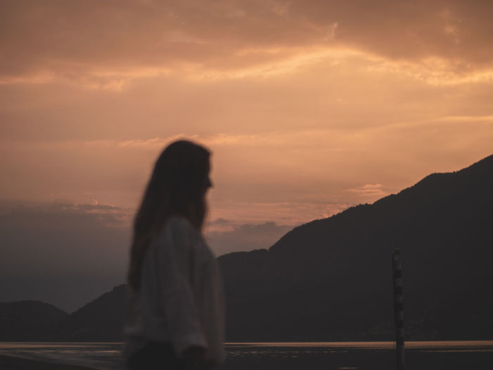 Woman standing on mountain against sky during sunset