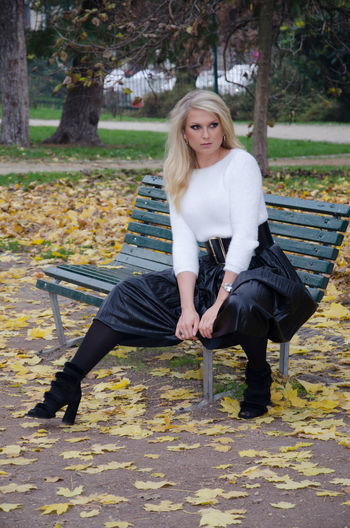 Young woman looking away while sitting on bench in park