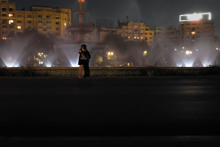 Couple Embracing By Fountain In City At Night