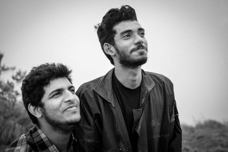 Smiling Friends Looking Away Against Sky