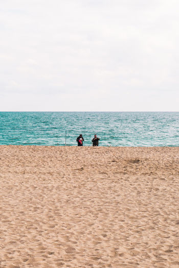 Sharing Adult Beach Beauty In Nature Bonding Day Fishing Fishing Time Horizon Over Water Leisure Activity Lifestyles Low Section Men Minimal Minimalism Nature Outdoors People Real People Rear View Sand Sea Sky Togetherness Two People Water
