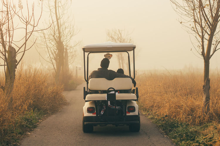 Rear View Of Father With Son In Golf Cart On Road Amidst Field During Foggy Weather