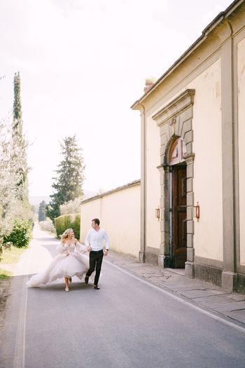 Full length of bride and groom running on street against sky