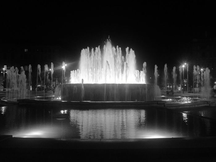 Fountain in city at night