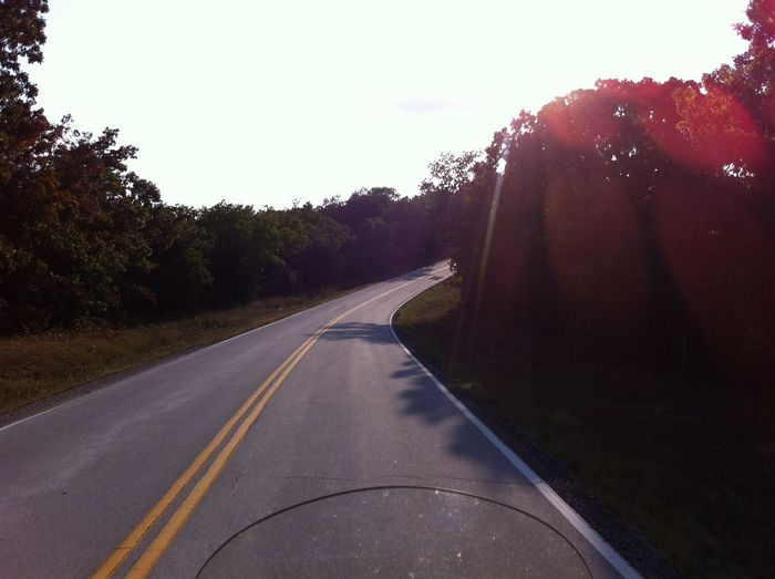 Empty curvy road  with lens flare