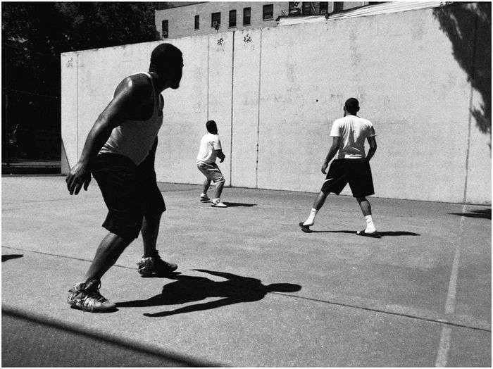 REAR VIEW OF PEOPLE PLAYING WITH BALL ON THE FLOOR