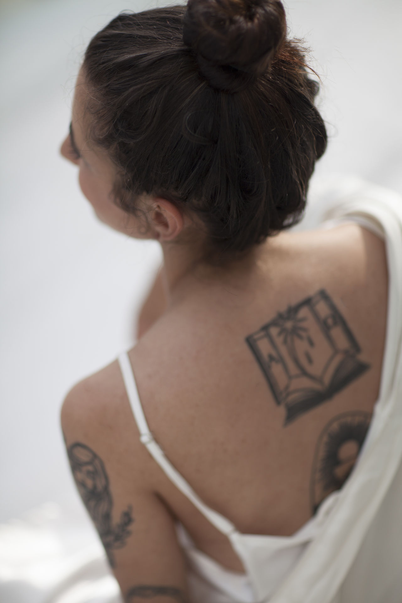 Rear view of young woman with tattoo sitting indoors