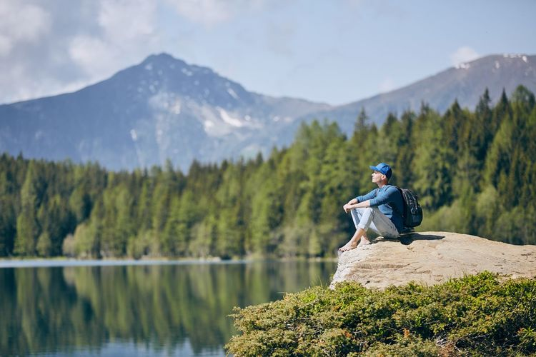 Young man (tourist) resting on rock above lake against mountain range of Alps. Pure nature in South Tyrol in Italy. Contemplation Exploring Thinking Tourist Travel Alps Carefree Enjoyment Italy Lake Landscape Men Mountain Mountain Range Nature One Person People Real People Relaxation Resting Rock - Object Scenics - Nature Tourism Tranquil Scene Water