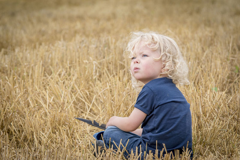 Agriculture Blond Hair Casual Clothing Childhood Day Field Focus On Foreground Grass Growth Innocence Leisure Activity Nature Outdoors Person Relaxation Rural Scene Selective Focus Summer Tranquility