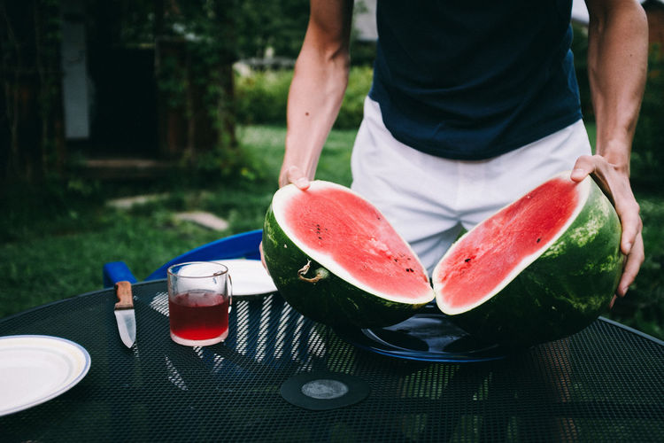 Midsection of man holding watermelon at table