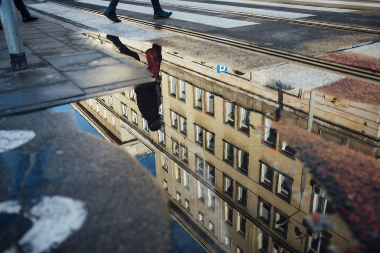 Reflection of person in puddle walking on street