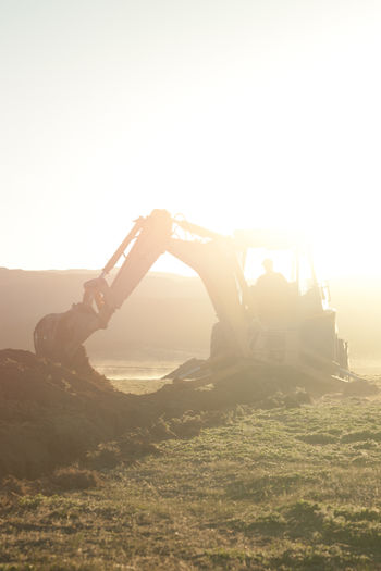 Backhoe at work Lens Flare Sunlight Silhouette Only Men One Man Only Sunset Outdoors One Person Adult People Men Tractor Backhoe Backhoe Loader Working Construction Digger Digging Holes
